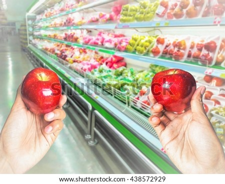 Concept,Two hand hold and choosing apple at fruits store in the supermarket background. - stock photo