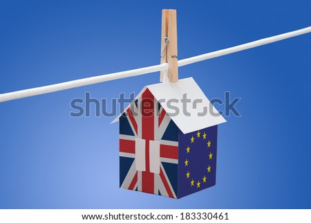 concept - UK, Britain and EU flag painted on a paper house hanging on a rope - stock photo