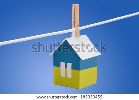 concept - Ukraine, Ukrainian flag painted on a paper house hanging on a rope - stock photo