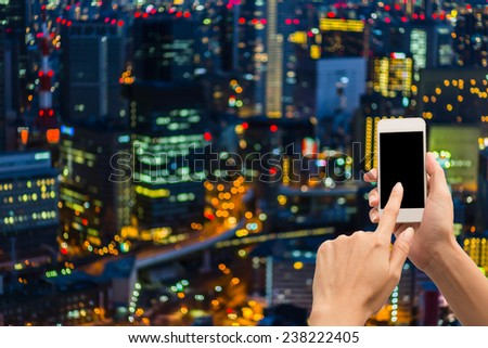 Concept using smartphone with abstract city light background. - stock photo