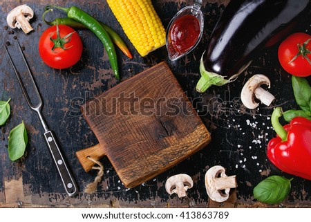Concept veggie BBQ background with assortment of raw vegetables, herbs, barbecue sauce, salt, small chopping board and meat fork over old black wooden surface. Flat lay.