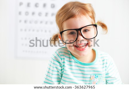 concept vision testing. child  girl with eyeglasses at the doctor ophthalmologist - stock photo