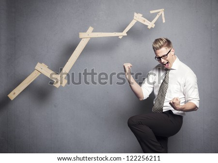 Concept: Winner in business. Thrilled young businessman cheering in front of positive business graph, isolated on grey background. - stock photo