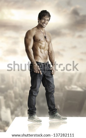 Concept winning portrait of a sexy smiling shirtless man on rooftop - stock photo