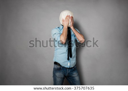 concept with a young man with face covered by a textile material covering eyes, on grey - stock photo
