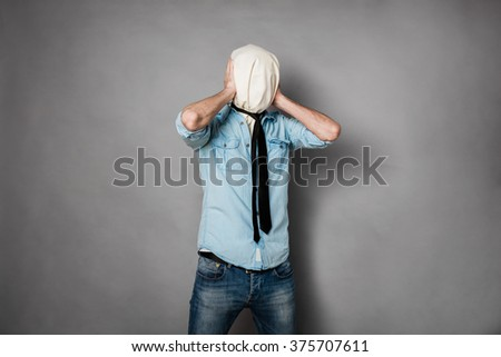 concept with a young man with face covered by a textile material covering his ears, on grey - stock photo