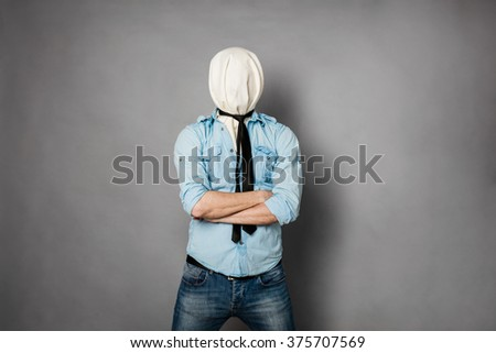 concept with a young man with face covered by a textile material crossing his arms - stock photo
