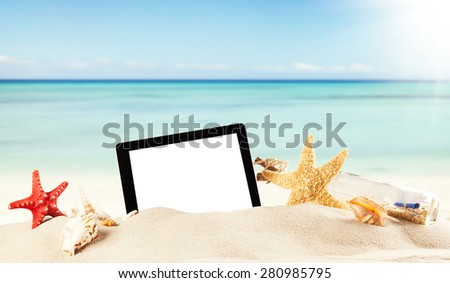 Concept with summer beach, tablet and accessories, blur sea on background - stock photo