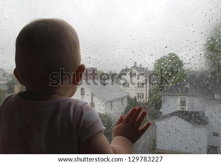Conception of loneliness and waiting Toddler waiting by window for parent to return