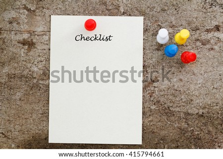 Conceptual,a piece of paper on a wooden table and pen with checklist word. - stock photo