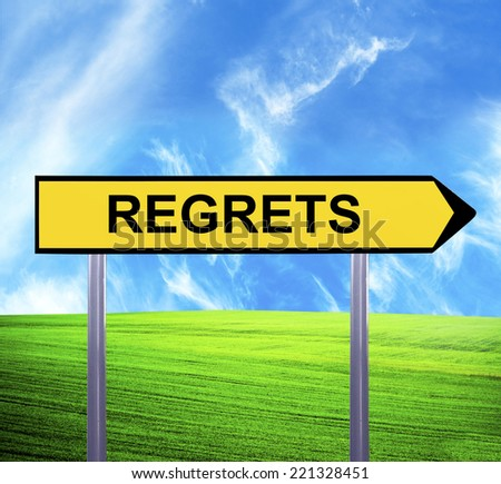 Conceptual arrow sign against beautiful landscape with text - REGRETS - stock photo