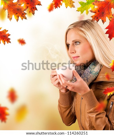 Conceptual autumn portrait of beautiful blond woman drinking tea with falling leaves around - stock photo