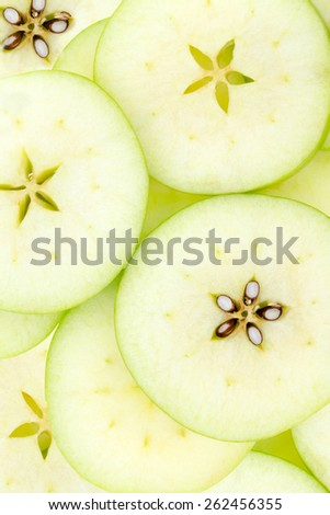 Conceptual background pattern and texture of sliced fresh green organic apples with the pip detail forming an attractive star to the center of each slice, overhead view - stock photo