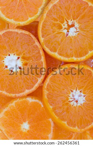 Conceptual background texture and pattern of slices of juicy succulent clementine overlaying each other in a full frame food background with central white coloration to the fruit - stock photo