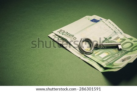 Conceptual composition, euro hundred banknotes with key as symbolic object.  - stock photo