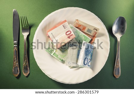 Conceptual composition, white plate full of euro money.  - stock photo
