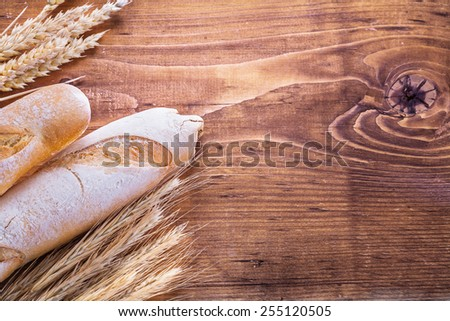 conceptual copyspace image baguettes and ears of rie wheat on vintage board  - stock photo
