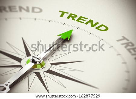 Conceptual 3D render image with depth of field blur effect. Compass needle pointing the green word trend over natural paper background.  - stock photo