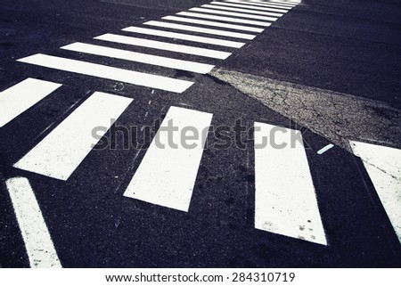 Conceptual danger and careful asphalt marking of pedestrian crossing background. Blue color tone used.  - stock photo