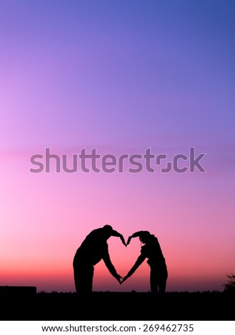 Conceptual heart shape, symbol of human. Woman and man hand silhouette over sky at sunset background, metaphor to love, valentine day, romantic, couple, wedding, romance, summer or sunrise - stock photo