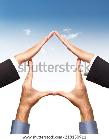 Conceptual home symbol made by hands in shape of house over blue sky and white background. Real estate, housing, construction industry, architecture and design concept. Isolated with clipping path. - stock photo