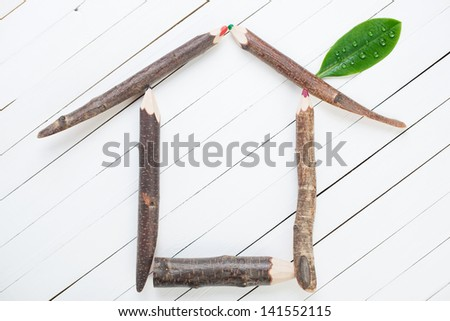 Conceptual house made up of wooden pencils and green leaf