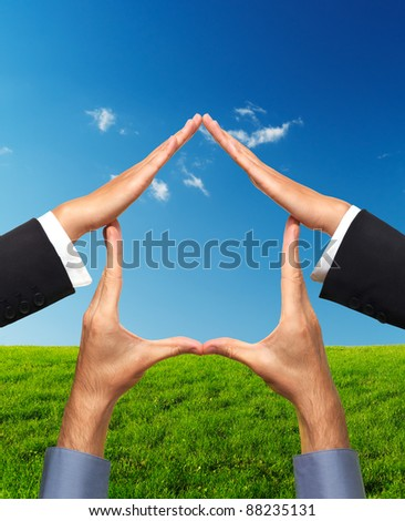 Conceptual house symbol made by hands over bright sunny landscape background. Real estate, housing, construction industry, architecture and design concept. Isolated with clipping path. - stock photo