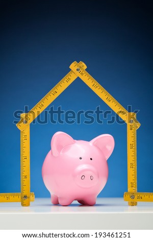 Conceptual image about savings and building a new home - yellow measurement tape in the shape of a house with a pink piggy bank inside it. - stock photo