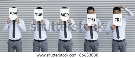 Conceptual image about the working week. Asian business man holding signs with the days of the week writen on them.