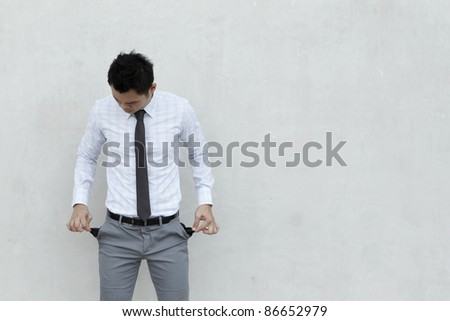 Conceptual image. Asian Businessman stands holding his pockets out showing he has no money. - stock photo