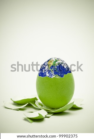Conceptual image. Birth of world concept. Ecology, Easter, new beginnings concept. Focus on egg. Earth in this montage provided by NASA (http://visibleearth.nasa.gov/) - stock photo