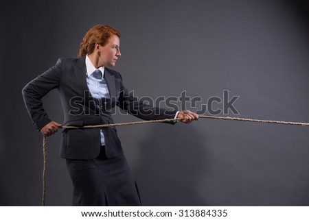 Conceptual image. Businesswoman pulling on a strong rope isolated on dark grey. Lady is not afrait of existing problems.