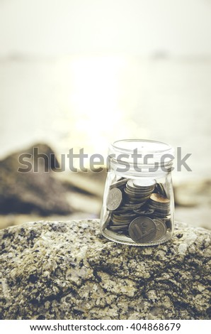 conceptual image.coin in glass jar on the rock. - stock photo