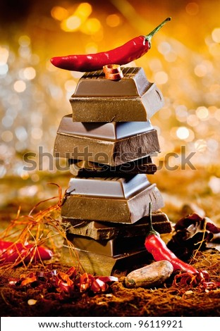 Conceptual image for red hot chocolate with a tower of chocolate cubes topped by a red hot chilli against a bokeh of festive lights - stock photo