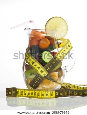 Conceptual image - fresh fruits and vegetables in a glass jug with measuring tape on a white background. - stock photo