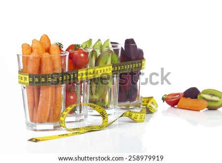 Conceptual image - fresh fruits and vegetables in glass cups with measuring tape on a white background. - stock photo