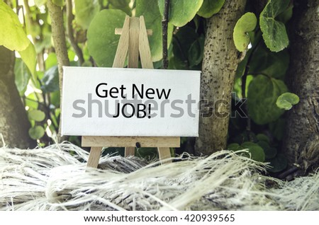 conceptual image, Get New Job word on white canvas and wooden easel.Green nature background and sunlight effect - stock photo