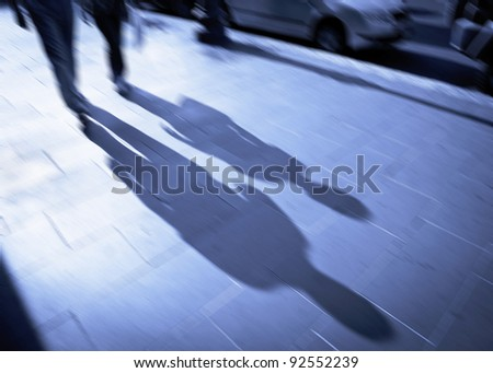 Conceptual image of a backlit couple on the move in the public room. Use your fantasy - make your story. Intentional motion blur. - stock photo