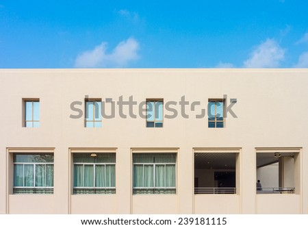 Conceptual image of a building and glass windows with blue sky - stock photo