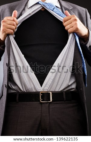 Conceptual image of a businessman tearing off his shirt over gray background - stock photo