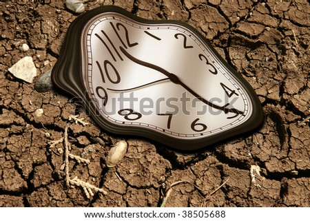 conceptual image of a clock on dried soil - stock photo
