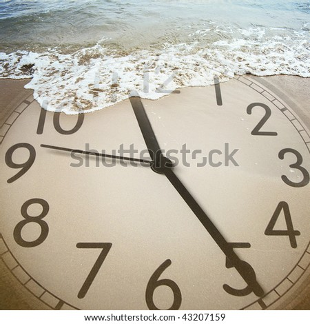 conceptual image of a clock on the beach - stock photo
