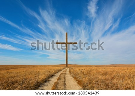 Conceptual image of a cross and a country road. - stock photo