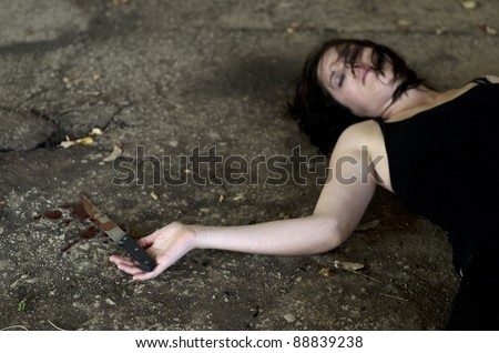 Conceptual image of a dead woman victim holding a sharp knife covered with blood. Concept photo of murder and crime - stock photo