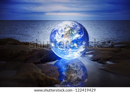 Conceptual image of a Glowing earth in a puddle at sea. Earth image provided by NASA. - stock photo