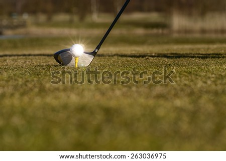 Conceptual image of a golfer teeing-off on the fairway with a low angle view of the ball on a tee and head of the driver on green grass with copy space - stock photo