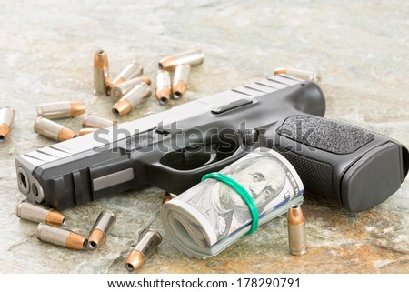 Conceptual image of a handgun with a roll of money surrounded by scattered bullets and cartridges on an old weathered wooden surface with copyspace depicting crime, a payoff, robbery or bribe - stock photo