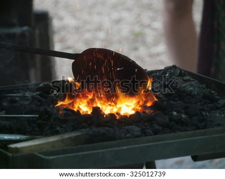 Conceptual image of a hot iron in burning coals - stock photo