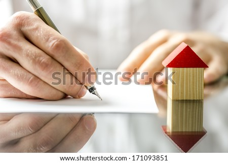 Conceptual image of a man signing a mortgage or insurance contract or the deed of sale when buying a new house or selling his existing one with a small wooden model of a house alongside - stock photo