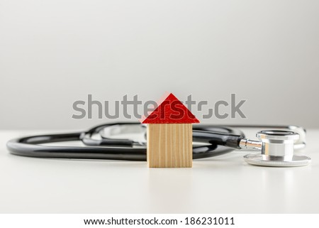 Conceptual image of a medical stethoscope lying on a white surface with a small wooden model of a house with a bright red roof with copyspace on grey above. - stock photo